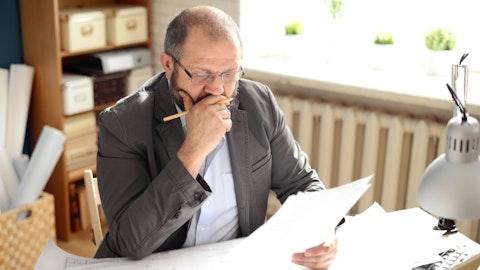 En entreprenør sitter og leser gjennom papirer mens han tenker hardt.