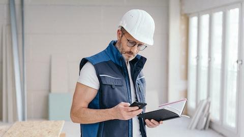 En entreprenør med hjelm sjekker mobilen sin.