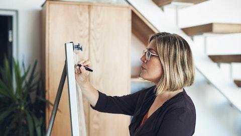 En kvinne med briller står og skriver noe på et whiteboard.