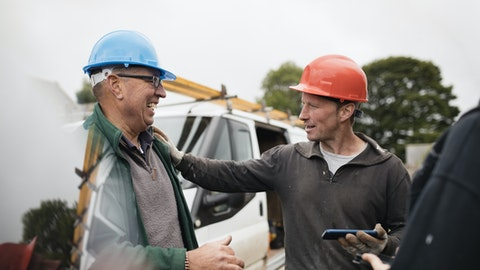 To entreprenører med hjelmer står og snakker sammen og ler.