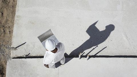 Fuglefoto av en entreprenør som står med en laptop ute.