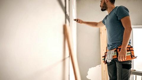 En entreprenør står og maler veggen i en leilighet.