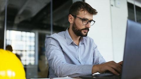 En konsentrert mann med skjegg og briller jobber på laptopen sin.