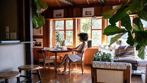 En kvinne som sitter ved et bord i feriehuset sitt.