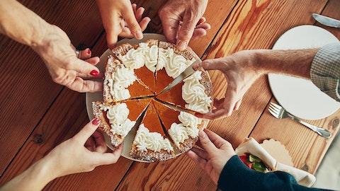 Seks personer forsyner seg av en kake.