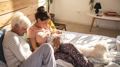 En mor sitter i sengen og holder babyen sin i armene, mens bestemoren sitter ved siden av henne.