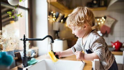 En liten gutt hjelper til med oppvasken