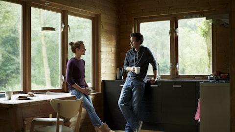 Et par står på stua i en hytte og holder en samtale med en kopp kaffe i hånden.