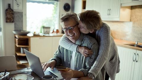 En kvinne holder rundt mannen sin mens han sitter på laptopen.