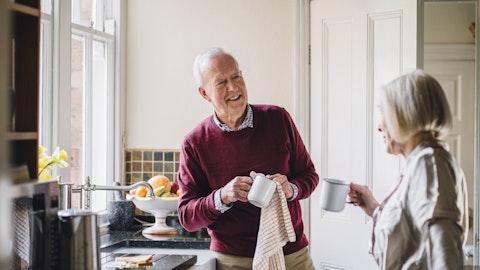 Et eldre par står på kjøkkenet og vasker opp.