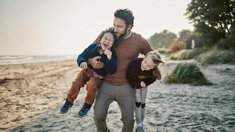 Mann med to barn på stranda