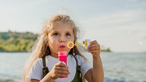 En jente med såpebobler på stranden.