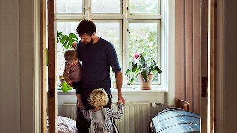 En far står foran et vindu med sine to små barn.