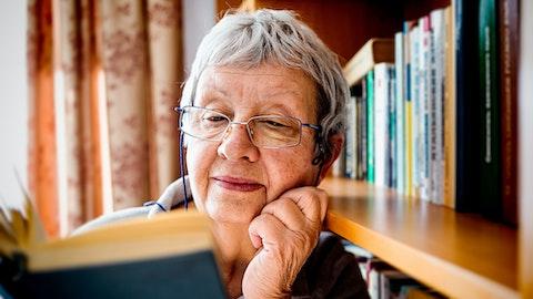 Eldre kvinne som leser en bok.