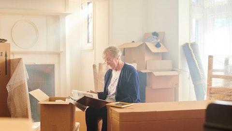 En eldre kvinne sitter blant masse flytteesker.