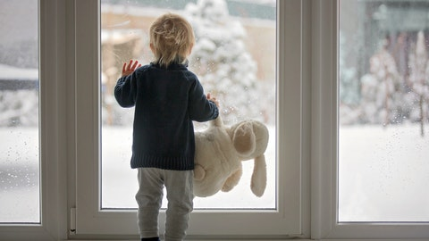 En liten gutt står og ser ut av verandadøren mens han holder en kosebamse.