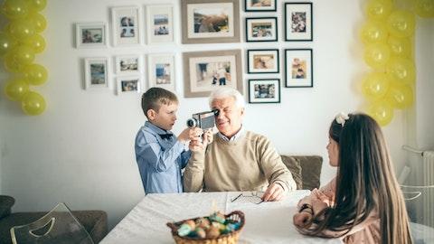 En gutt hjelper bestefaren sin med et filmkamera.