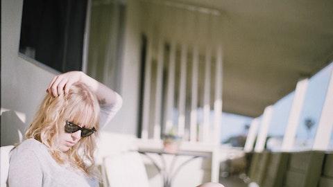 En kvinne med solbriller sitter på terrassen.
