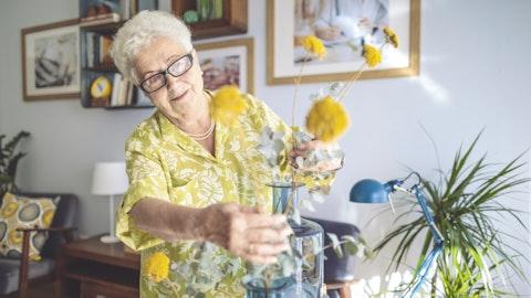 En eldre dame fikser blomster i en vase.