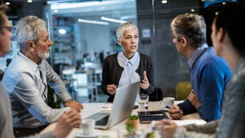 Forretningskvinne fører et møte ved et bord med medarbeidere eller klienter