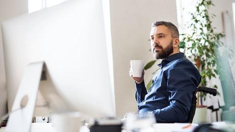 Mann med kaffe i hånden og ser konsentrert på en PC-skjerm