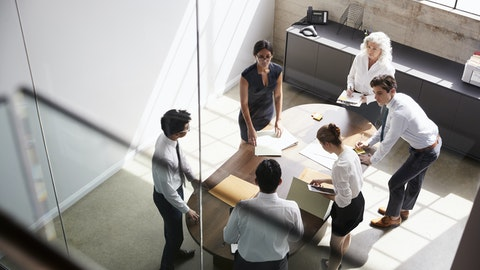 En gruppe mennesker står rundt et bord og diskuterer.