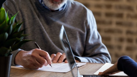 Mann skriver under på en kontrakt.