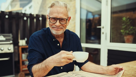 Smilende mann som drikker kaffe og leser avisen