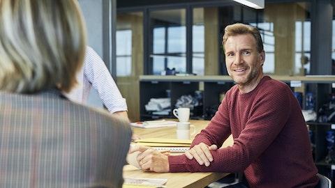 En mann sitter ved et bord og ser på kameraet.