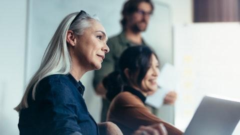 En smilende kvinne under et møte med flere deltakere.