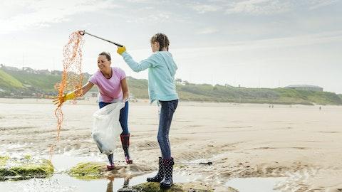 To kvinner fisker plast fra vannet ved stranden
