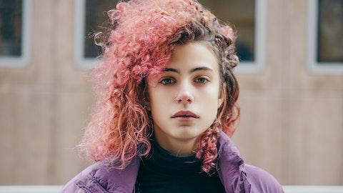 En ung kvinne med rødt hår og nesering ser alvorlig mot kameraet.