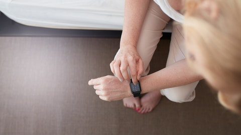 En kvinne taster inn noe på smartklokken sin.