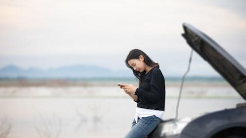 En kvinne ser på mobilen foran en bil.