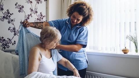En sykepleier hjelper en kvinnelig pasient med å kle på seg.