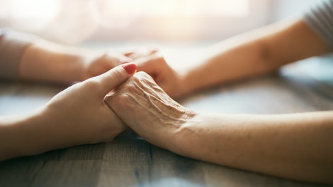 En eldre og en yngre kvinne holder hender over et bord.