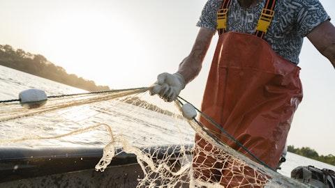 En fisker er ute på en båt og arbeider.