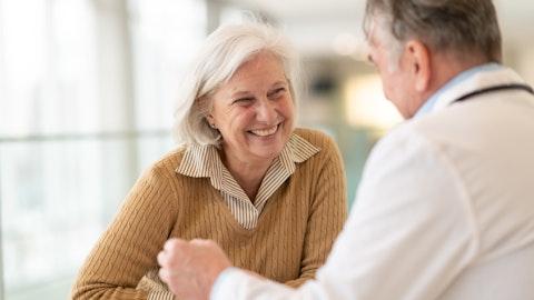 Eldre kvinne smiler i samtale med legen.