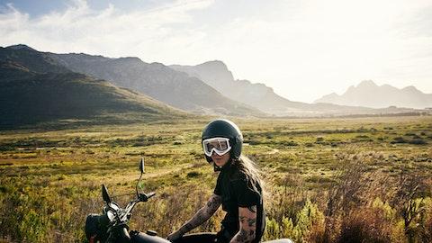 kvinne på motorsykkel, bakgrunn er åpen natur