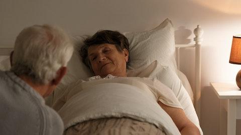 En eldre mann ser på konen sin som ligger i sengen.