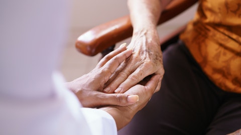En sykepleier holder hånden til en eldre dame.
