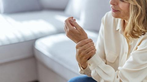 kvinne holder i håndleddet, ser ut som om hun har smerter