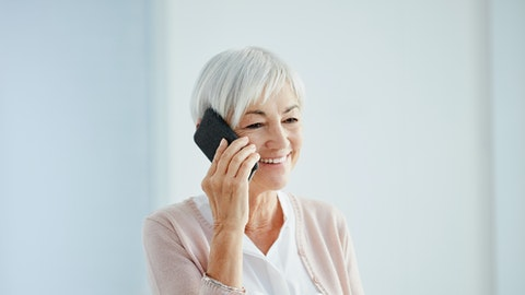 Eldre kvinne som snakker i mobil.