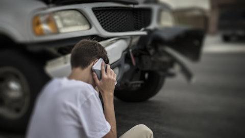 Gutt som snakker i telefon foran en bil som har kræsjet.
