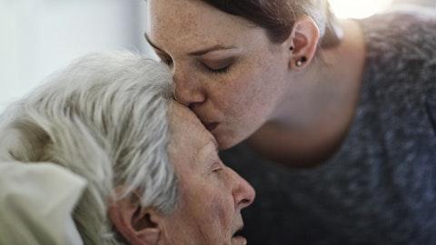 En datter kysser sin eldre mor på pannen.
