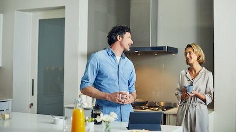 Et par står på kjøkkenet og snakker sammen.