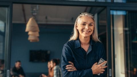 En kvinne smiler mot kameraet med mobilen i hånden.