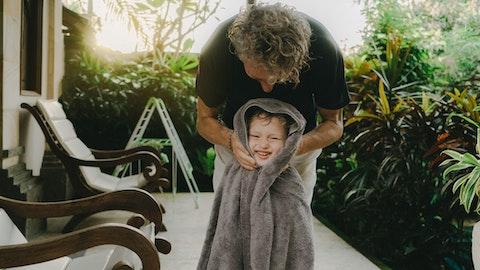 En mann står på verandaen og holder et håndkle rundt sønnen sin.