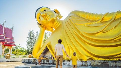 En mann holder sønnen sin i hånden foran en stor Buddha.