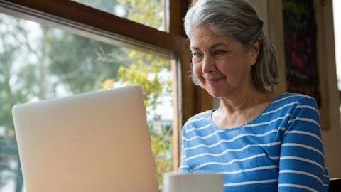 En eldre kvinne sitter på laptopen.